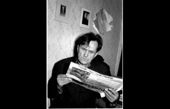 Шаламов читает газету. На стене – фотография Осипа Мандельштама. 1968 год